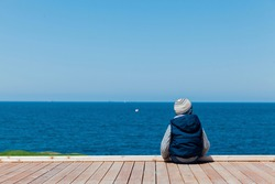 Little boy sits alone and looks at the ships in the sea