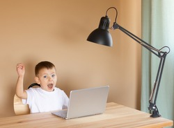 Little boy sits at a laptop and rejoices and raises his hand up