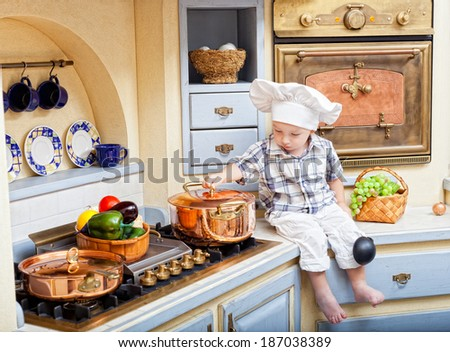 little boy sits on a kitchen table and plays the cook