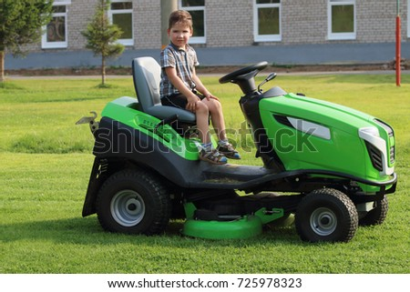 Little boy sits on lawn on green grass near building at summer day #725978323