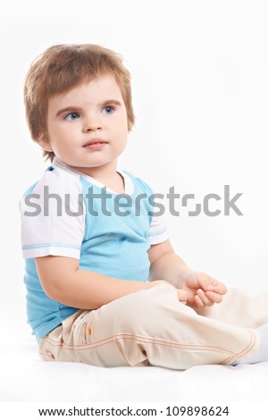 little boy sits on the floor and curiously looking