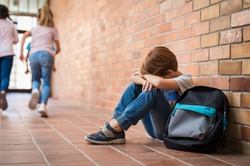 Little boy sitting alone on floor after suffering an act of bullying while children run in the background. Sad young schoolboy sitting on corridor with hands on knees and head between his legs.