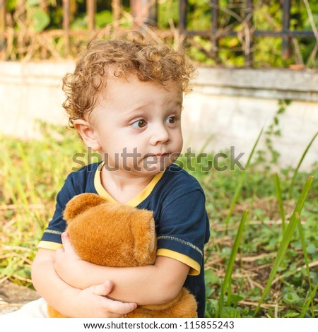 little boy sitting and playing with a toy