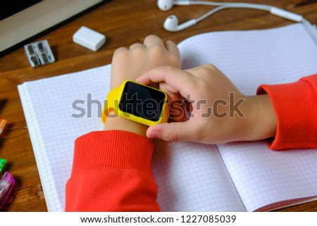 Little boy sitting at the table and looking smart watch. Smart watch for baby safety. The child makes school lessons, listening to music, calling friends.