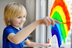 Little boy sitting at window with drawing rainbow while coronavirus quarantine. Rainbow sign is symbol of hope, means that everything will be OK. Stay at home for lockdown coronavirus.