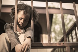 Little boy sitting behind the fence. Homeless orphan stressful kids, education sickness human right day concept
