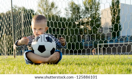 Little boy sitting cross legged on the ground in the goalposts with a soccer ball balanced on his lap