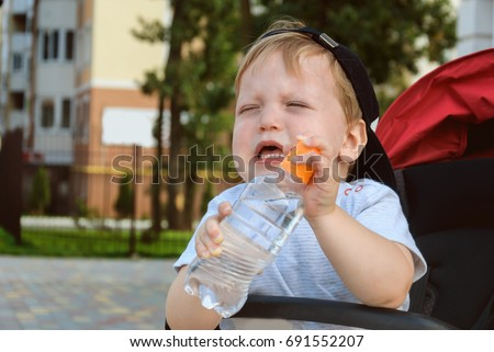Little boy sitting in a pram and holding a drinking water bottle and capricious (crying)