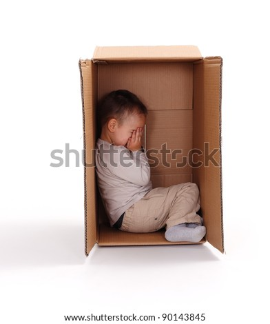 Little boy sitting in cardboard box, hiding his face with hands