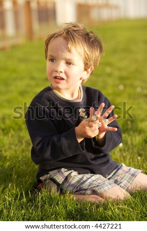 Little boy sitting in the grass picking clover with a cute expression on his face