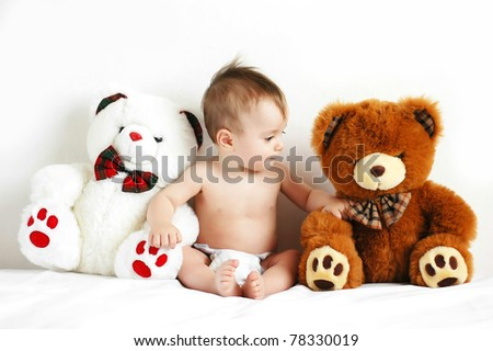 Little boy sitting next to a teddy bears