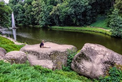 Little boy sitting on a huge stone in front of the lake and looking at the Snake fountain, dendrological park Sofiyivka, Uman Ukraine.