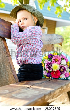 Little boy sitting on a wooden garden bench with a colourful bouquet of flowers waiting patiently for his mother to arrive so that he can give her his gift for Mothers Day or her birthday