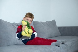 Little boy sitting on bed with plush dragon. Boy sitting on the bed at home and holding a plush dragon.