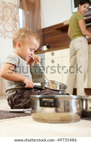 Little boy sitting on carpet in kitchen playing with cooking pots, mother preparing food in background.