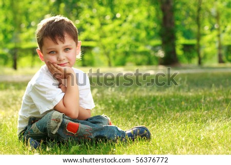 little boy sitting on grass