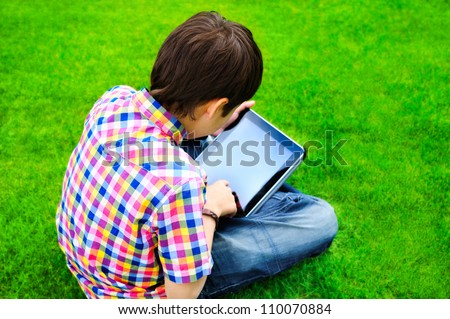 Little boy sitting on grass and using tablet computer
