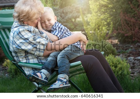 Little boy sitting on the arms of his beloved grandmother.Kisses and gentle hugs.Weekend in a country house.