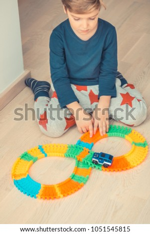 Little boy sitting on the floor and playing with car toy at home.  #1051545815