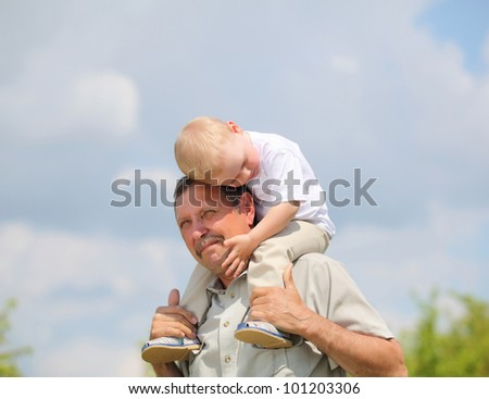 little boy sitting on the shoulders of his grandfather