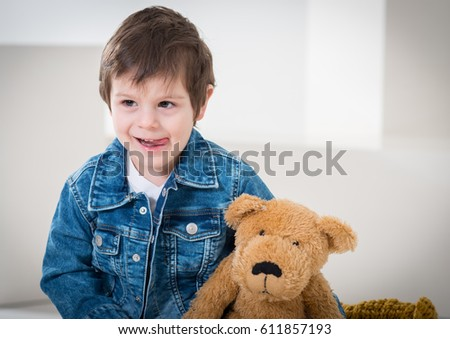 Little boy sitting on the travel retro brown suitcases in  jeans jacket with a bear