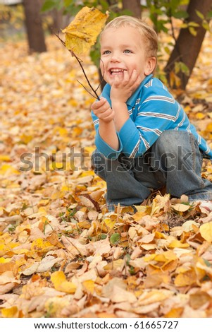 Little boy sitting on yellow autumn foliage, park.