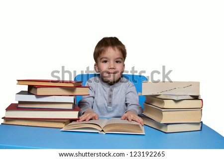 little boy sitting with books for a blue table