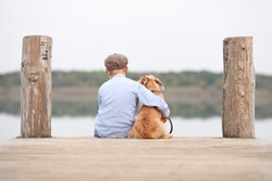 little boy sitting with his dog on the shore of Lake, child hugging his dog