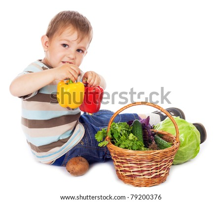 Little boy sitting with two paprika and basket of vegetables, isolated on white