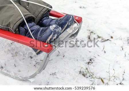 Little boy sledding in the winter