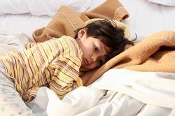 Little boy sleeping on bed in morning sun Shines.