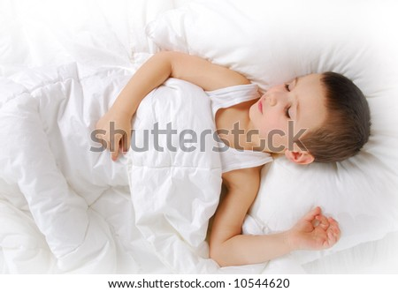 little boy sleeping  on the white bed