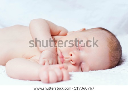 Little boy sleeping on white blanket