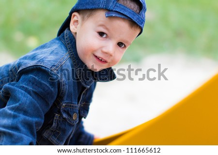 Little boy smiling on slide