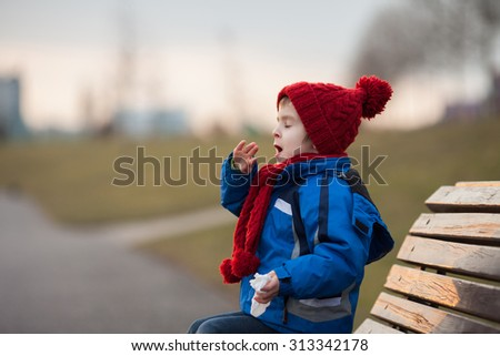 Little boy, sneezing and blowing his nose outdoor on a sunny winter day, sitting on a bench