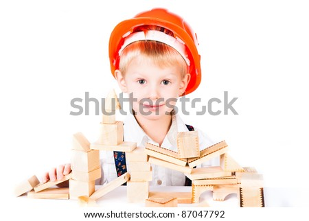 little boy stacks house from wooden blocks isolated on white background