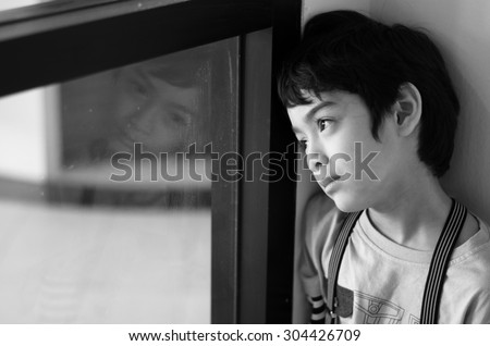 Little boy standing behind the window black and white