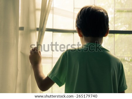 Little boy standing behind the window vintage