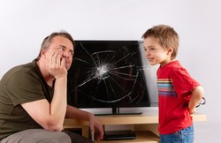 Little boy standing in front of a TV with broken screen and hiding a slingshot behind his back while his father looking at him angrily.