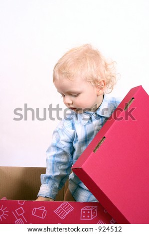 Little boy standing in toys box