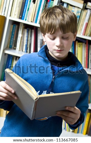 Little boy  standing near the bookshelf