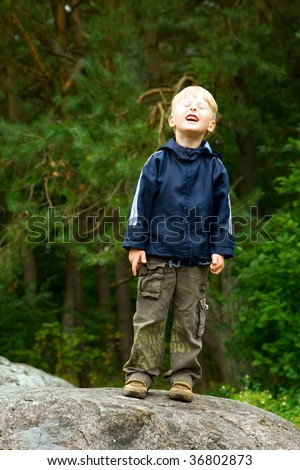 little boy standing on a stone and grimacing