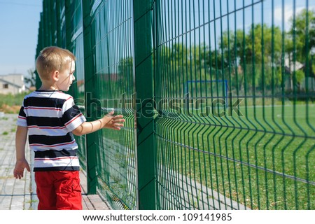 Little boy standing outside of sport field near grid fence