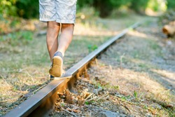 Little boy steps on the rails of the railway, being exposed to danger. Young boy balancing on a train rail.