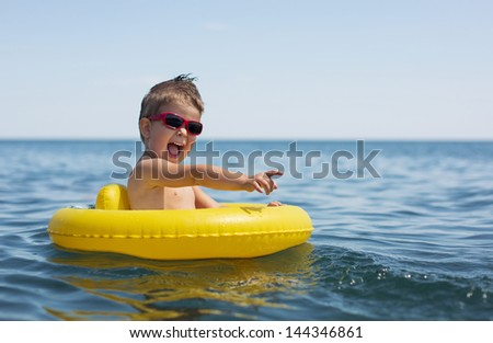 Little boy swimming and playing at sea