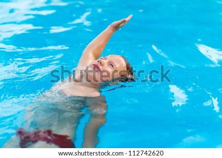 Little boy swimming, backstroke
