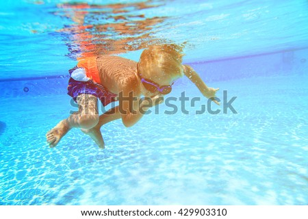 little boy swimming underwater #429903310