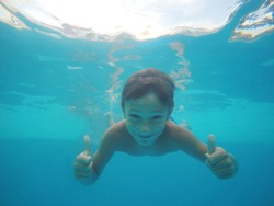 Little boy swimming underwater in pool