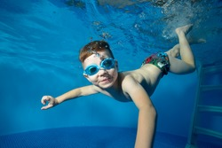 Little boy swims underwater in the pool, smiling, blowing bubbles and looking at me. The view from under the water. Close-up. Horizontal orientation