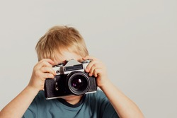 Little boy taking photo with old film camera. Retro technology concept with copy space.